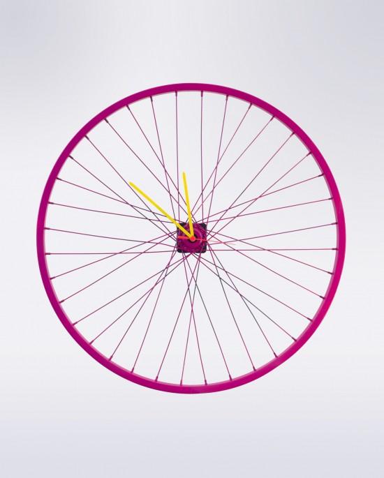 El reloj de pared Violet tiene un divertido diseño con radios dobles en color violeta y manillas en amarillo