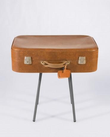 Mesa vintage compuesta por cuatro patas metálicas y una antigua maleta de piel color camel