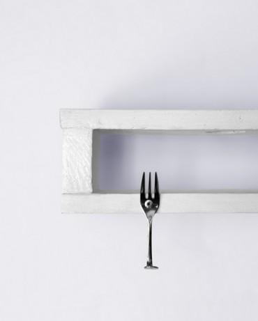 Colgador de madera pintada en blanco con tenedores como ganchos